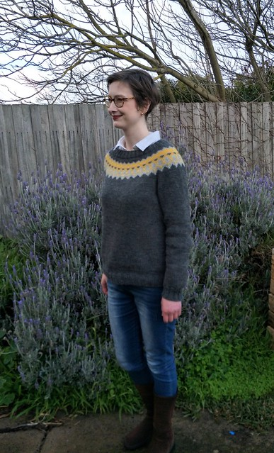 A woman stands in front of a garden fence. She wears a yellow and grey colourwork yoke Icelandic jumper, blue jeans and brown suede boots.