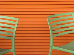 Green chairs and orange wall