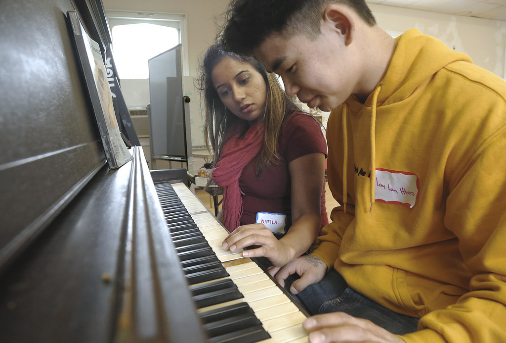 Najila Ahsan (B.S. URS '19), left, takes a break at the piano, with a community member.