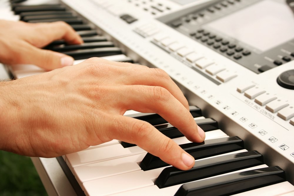 close-up photo of pianist's hand at electronic keyboard
