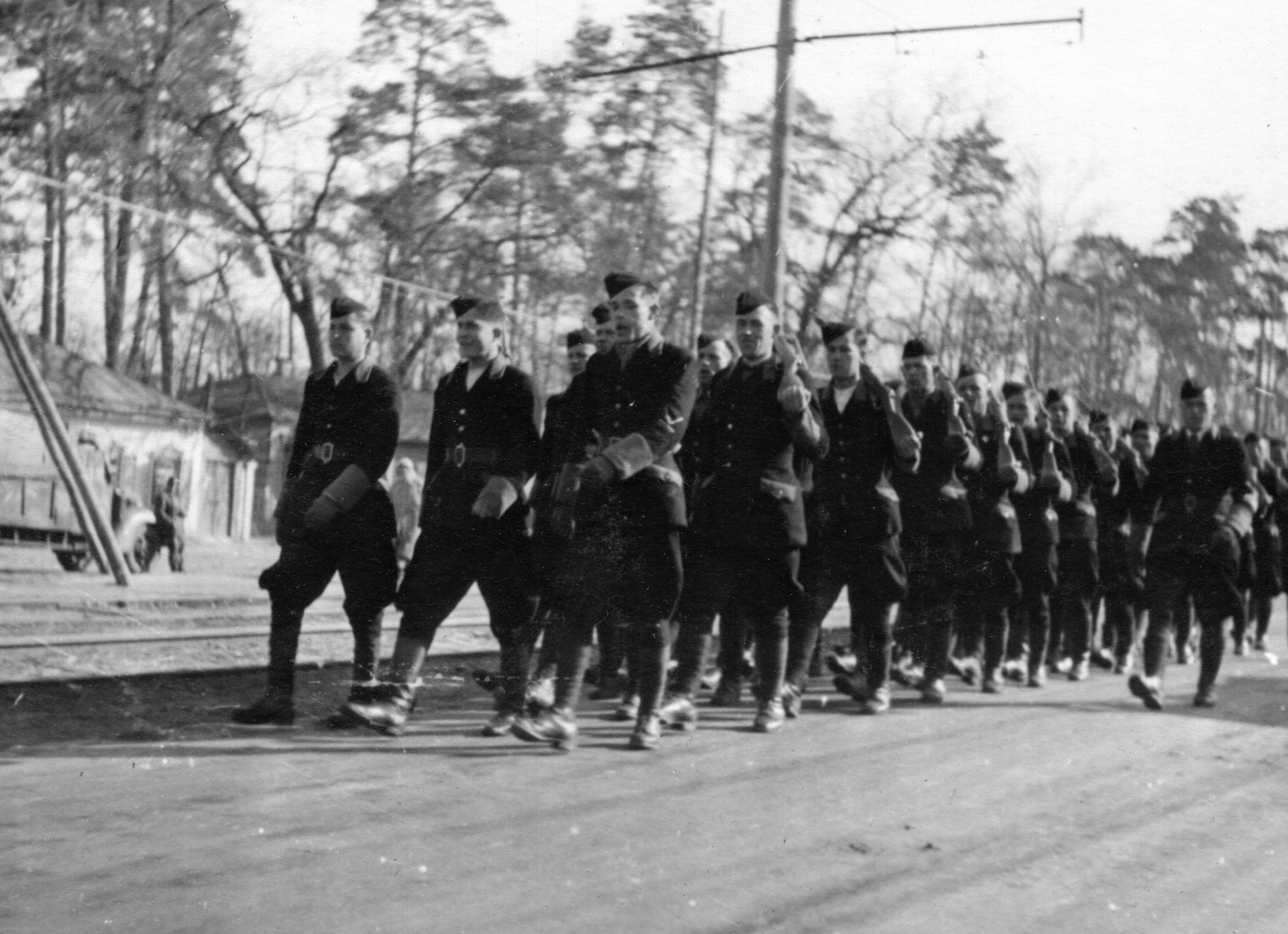 1943. Колонна солдат украинской вспомогательной полиции проходит строем по улице города