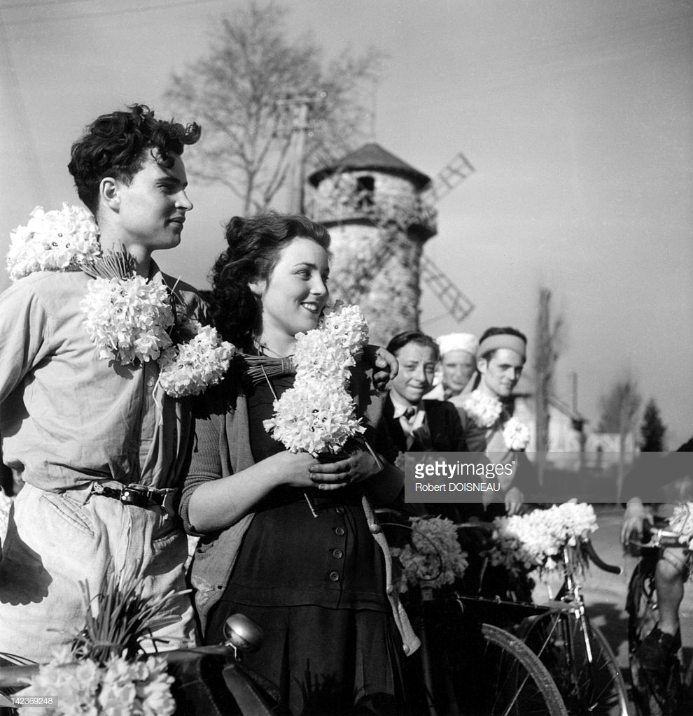 1947. Люди с гирляндами из нарциссов на дороге в Монжерон