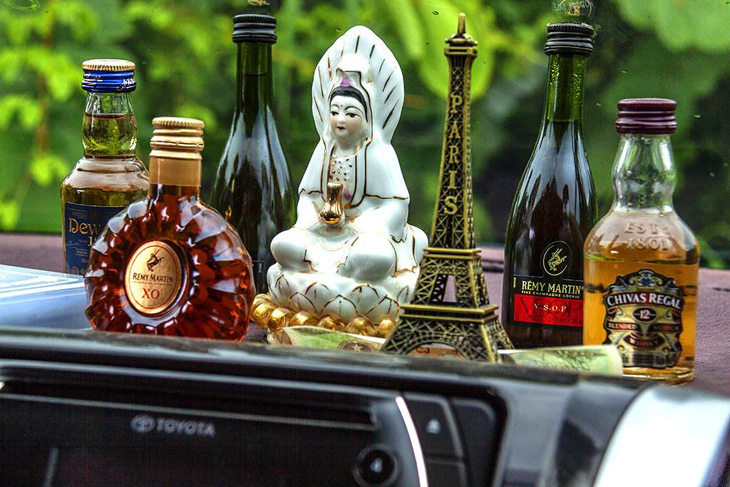 Female bodhisattva and liquor bottles on dashboard--Saigon