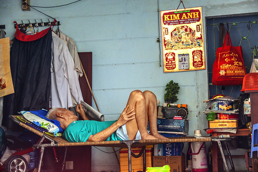 Old man on cot, reading--Saigon