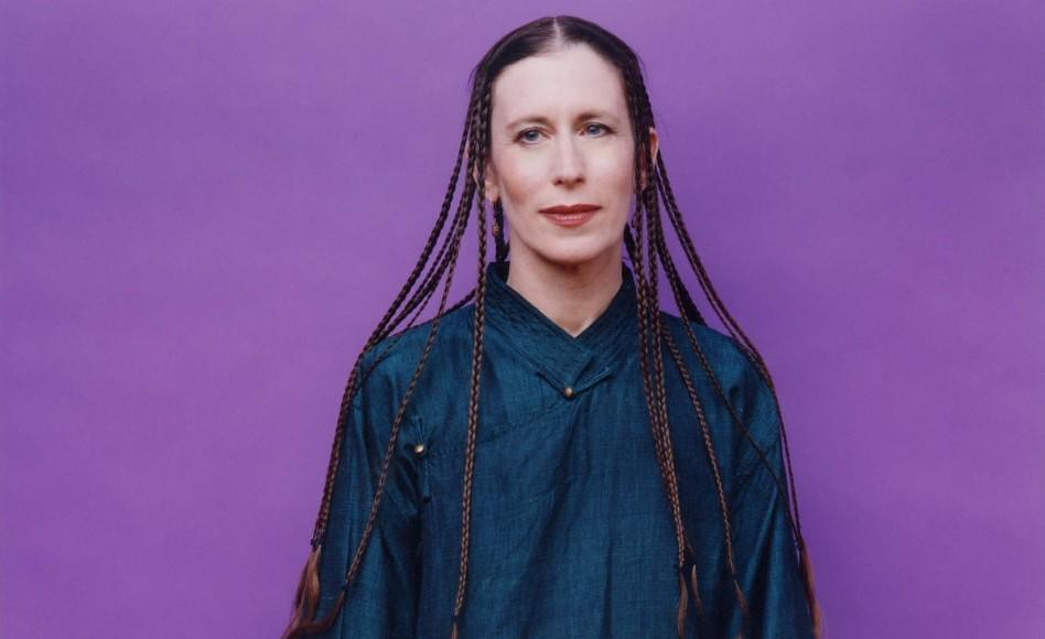 Meredith Monk standing in front of purple background