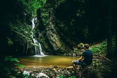 Man sitting and watching small waterfall