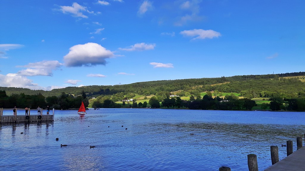 a red sailboat on Coniston Waters in the Lake District, England