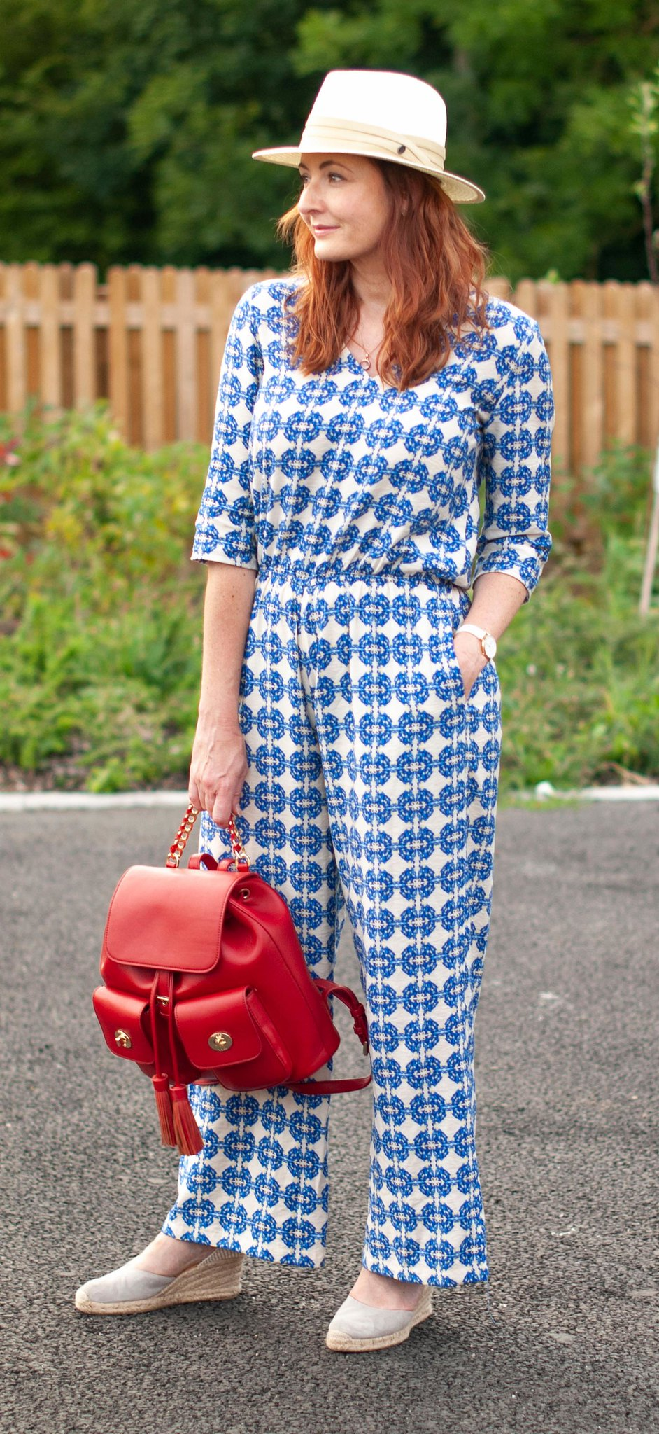 Like Nothing Else in the Shops: A Blue Patterned Jumpsuit \ grey wedge espadrilles \ cream Panama hat \ red backpack | Not Dressed As Lamb, over 40 style