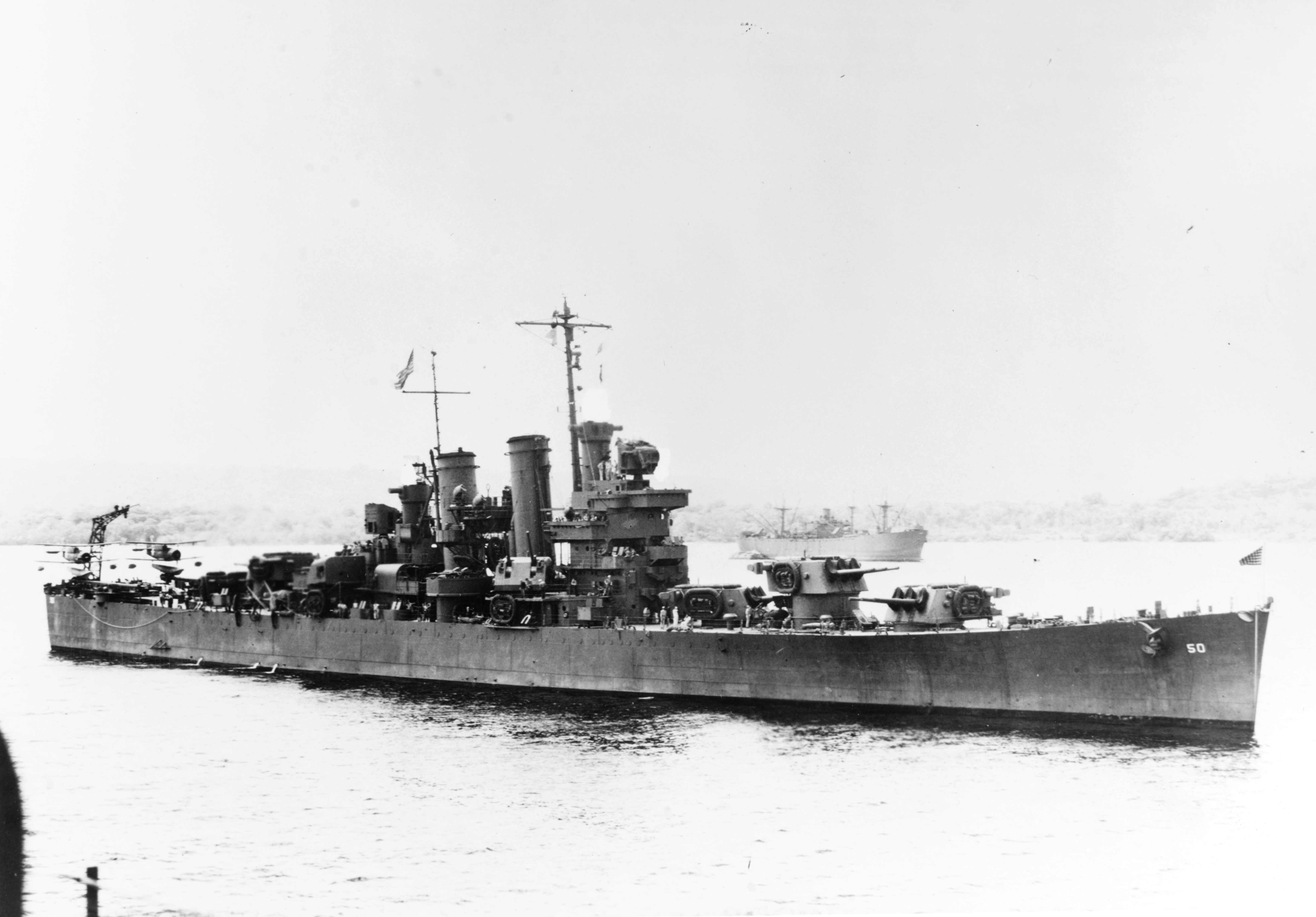 The U.S. Navy light cruiser USS Helena (CL-50) at a South Pacific base, between battles, circa in 1943. This image has been retouched to remove radar antennas from the gun directors and masts. The Helena was part of Task Force 64 under Norman Scott in the Battle of Cape Esperance.
