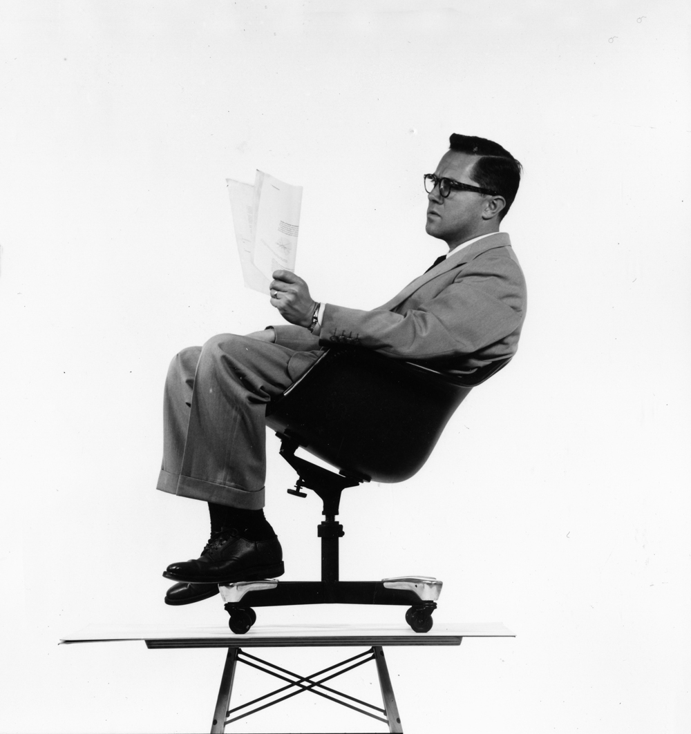 man sitting on chair on top of table, reading a piece of paper