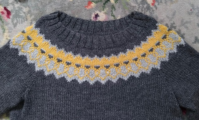 A yellow and grey colourwork jumper is laid flat on a patterned carpet.