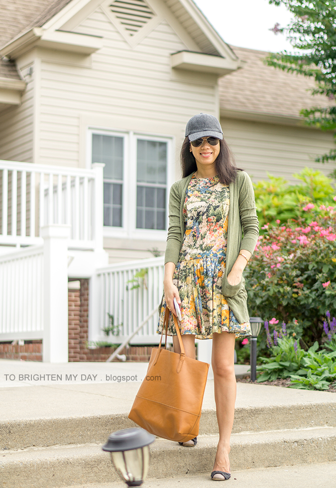 gray baseball cap, watercolor floral drop waist dress, green long cardigan, gold bangle, cognac brown tote, bow ballerina flats
