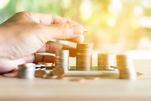 Hand put coins to stack of coins saving money and income or investment ideas and financial management for the future.