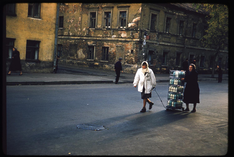 Женщины везут по улице тележку, полную бутылок с молоком