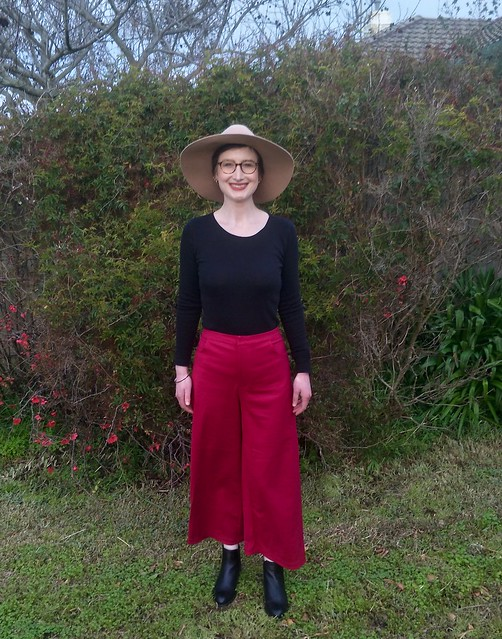 A woman stands against a garden fence. She wears magenta wide leg crop pants, a black skivvy, black ankle boots, and a tan felt hat.