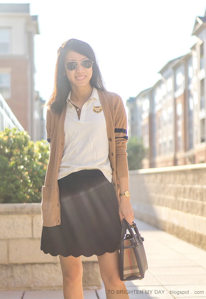 camel long varsity cardigan, polo with crest emblem, navy scallop skirt, gold watch, navy tote
