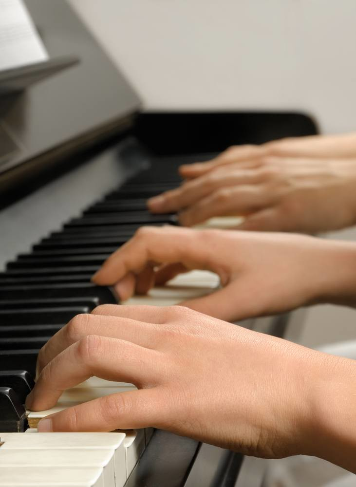 four hands playing a piano