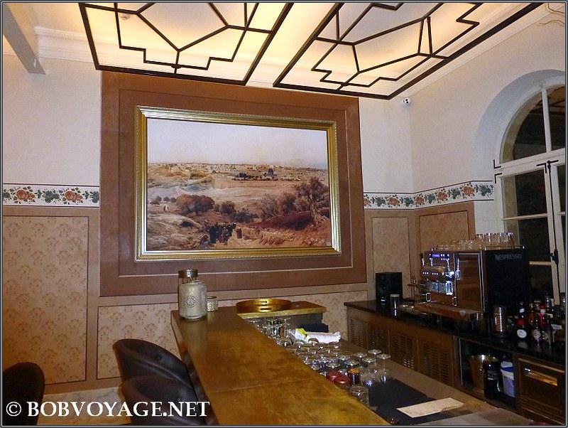 """רפרודוקציה ממוסגרת של הציור """"ירושלים"""" ב-בר של בית המלון"""