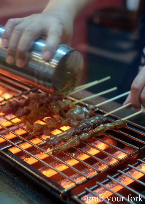 Seasoning skewers on the bbq at Granny Wolf BBQ in Central Park Mall Sydney