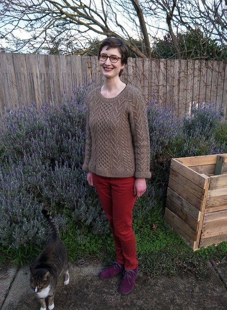 A woman stands in front of a garden fence. She wears a handknit cabled jumper, red jeans and purple boots. She is smiling. A cat stands next to her.