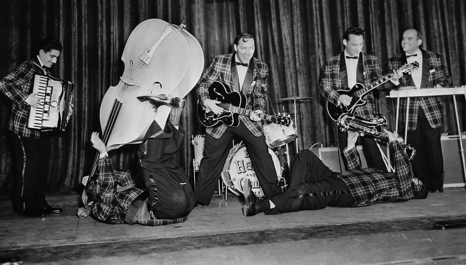 Bill Haley & His Comets rehearse at the Dominion Theatre in London, where they will open their British tour. The Comets include accordion player Johnnie Grande, bassist Al Rex, and saxophonist Ruddy Pompilli.