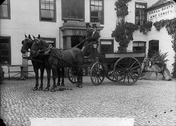 Two men in top hats sitting on a brake carriage drawn by two horses, circa 1895.