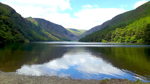 View across a lake surrounded by green hills - Glendalough Upper Lake, Wicklow, Ireland