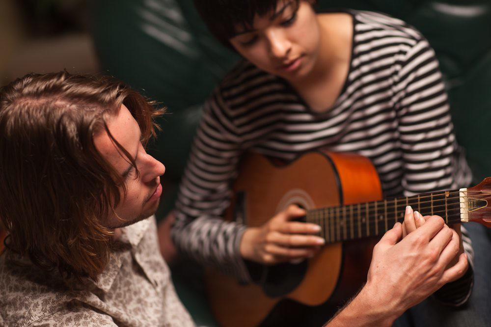 photo of musician teaching a guitar lesson