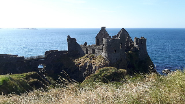 Ruins of Dunluce Castle, Northern Ireland, perched on a cliff overlooking the blue ocean.