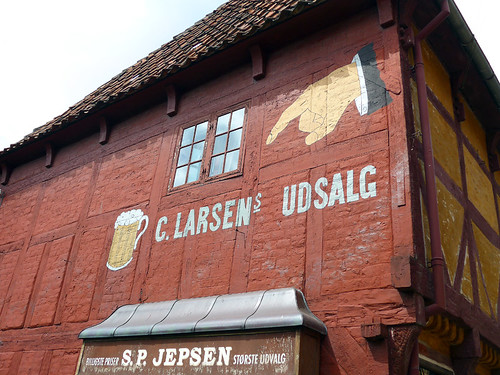 'Beer Here', an old style poster on red brick half-timbered building in Den Gamle By, recreated villages set in different times, in Aarhus, Denmark