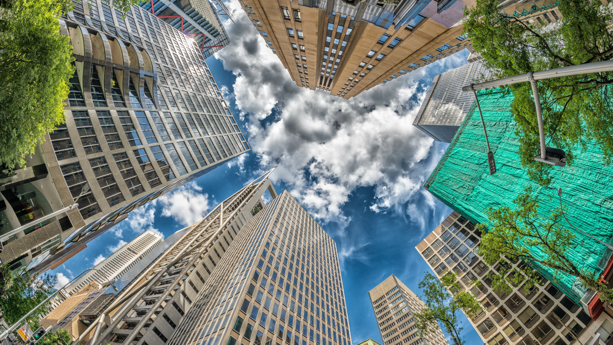 A worm's eye view of some skyscrapers reaching into a blue sky