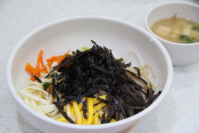 A bowl of bibimbap. Noodles topped with shredded vegetables and seaweed.