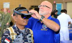 PEARL HARBOR, Hawaii (June 29, 2018) Mark Griffith, Joint Tele-Critical Care Network, fits a Republic of Indonesia sailor with a virtual reality headset during the Rim of the Pacific (RIMPAC) 2018 Inaugural Innovation Fair, June 29. This event is focused on providing an opportunity among government entities and government-sponsored academic institutions (U.S. and foreign) to display, demonstrate, and explain capabilities and technology they have recently or are presently developing. Twenty-five nations, more than 45 ships and submarines, about 200 aircraft, and 25,000 personnel are participating in RIMPAC in and around the Hawaiian Islands and Southern California. The world's largest international maritime exercise, RIMPAC provides a unique training opportunity while fostering and sustaining cooperative relationships between participants critical to ensuring the safety of sea lanes and security in the world's oceans. (U.S. Navy photo by Mass Communication Specialist 1st Class Jason Abrams/Released)