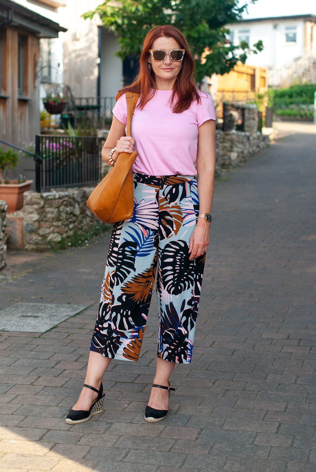 Wearing Pink With Red Hair in Summer \ candy pink t-shirt \ palm print culottes \ black wedge espadrilles \ tan hobo bag | Not Dressed As Lamb, over 40 style
