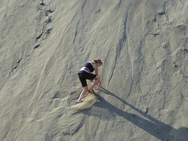 A intrepid traveller climbing up a massive sand dune in a remote island in Fiji