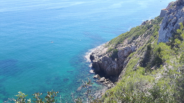 Looking down a mountainside to clear, turquoise Mediterranean Sea in Denia, Spain.