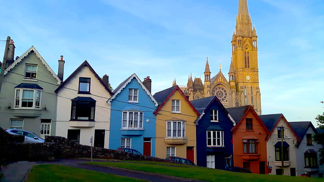 Row of brightly coloured houses on a hill with a tall cathedral behind in Cobh, County Cork, Ireland