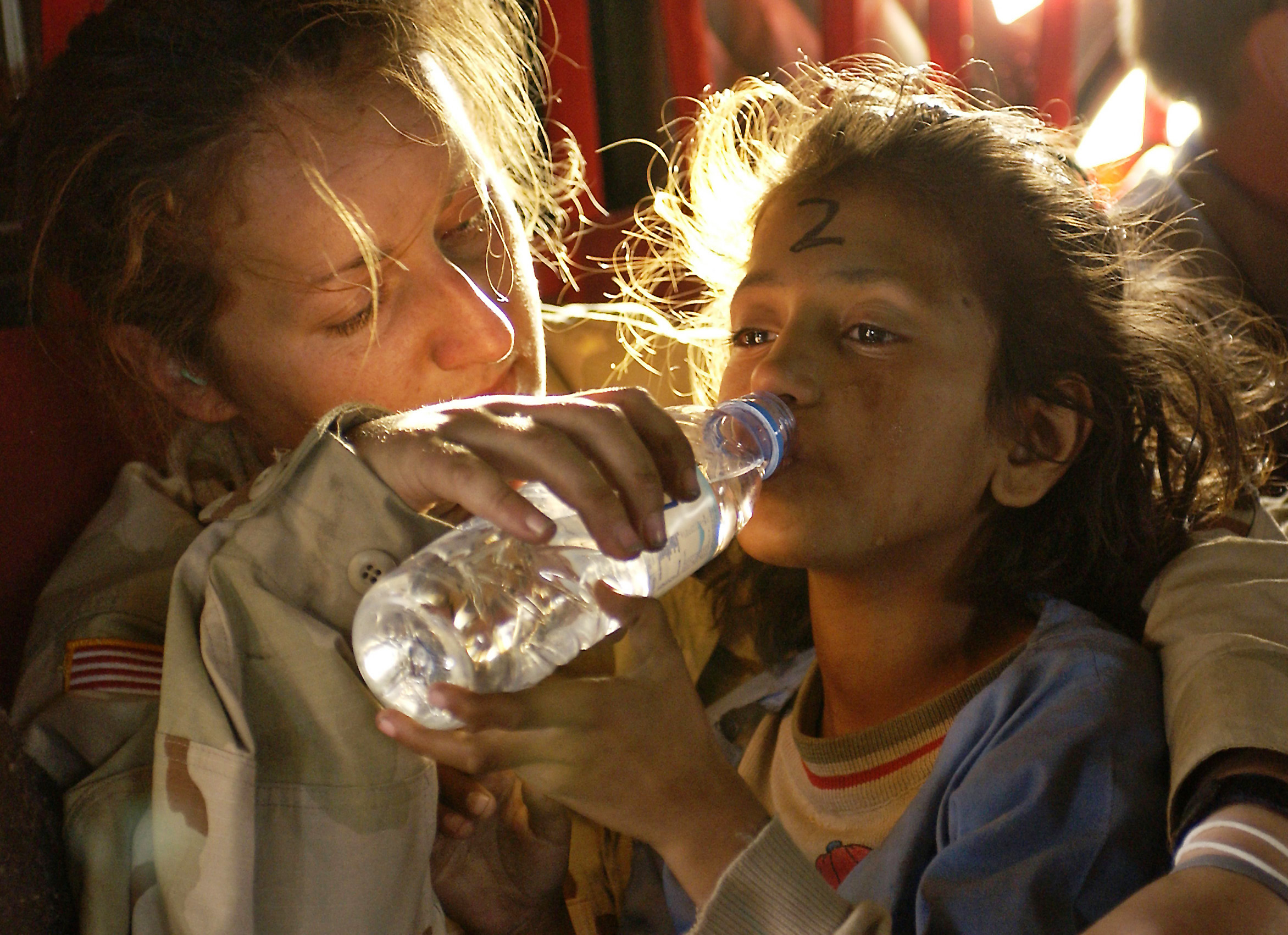 U.S. Army Sergeant Kornelia Rachwal gives a young Pakistani girl a drink of water as they are airlifted from Muzaffarabad to Islamabad, Pakistan, aboard a U.S. Army CH-47 Chinook helicopter on October 19, 2005.