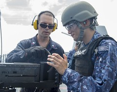 PHILIPPINE SEA (Aug. 15, 2018) Gunner's Mate 2nd Class Matthew Spano, left, instructs Japan Maritime Self-Defense Force Ensign Taisei Sakai, assigned to JS Kirishima (DDG 174), during a live-fire exercise with a M2HB .50 caliber machine gun aboard USS Antietam (CG 54). Antietam is on patrol in the U.S. 7th Fleet area of operation supporting security and stability in the Indo-Pacific region. (U.S. Navy photo by Mass Communication Specialist 2nd Class William McCann/Released)