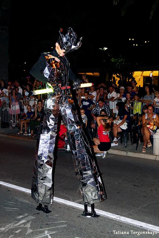 Человек в зеркальном костюме на ходулях