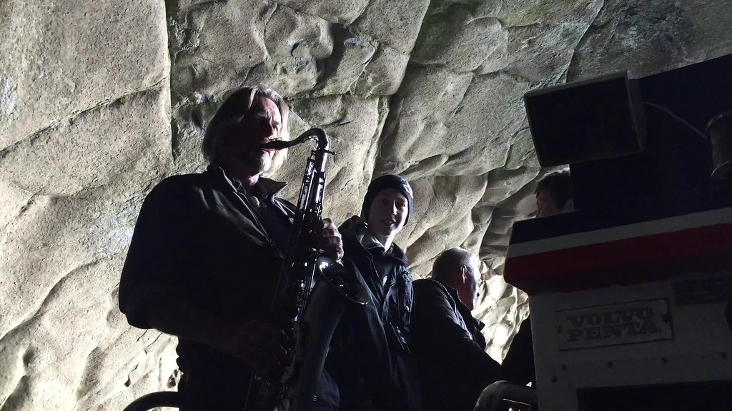 Playing saxophone to demonstrate acoustics in a cave