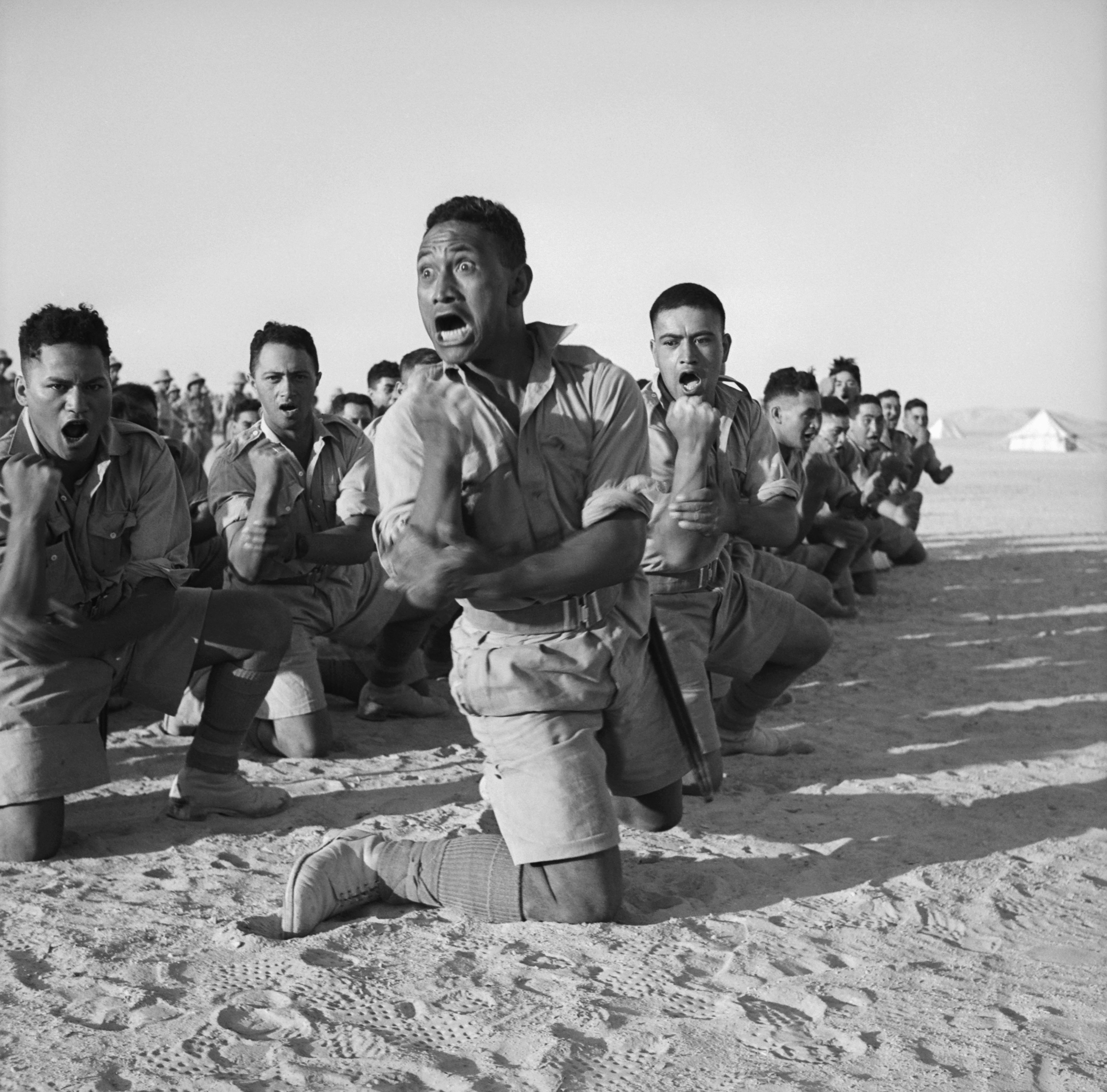 Māori Battalion survivors of action in Greece, performing a haka in Helwan, Egypt for the King of Greece. From left to right, the four men in the foreground are John Manuel, Maaka White, Te Kooti Reihana, and Rangi Henderson. Photo taken by unidentified New Zealand official photographer around June 24, 1941. From the collections of the Imperial War Museum and National Library of New Zealand.