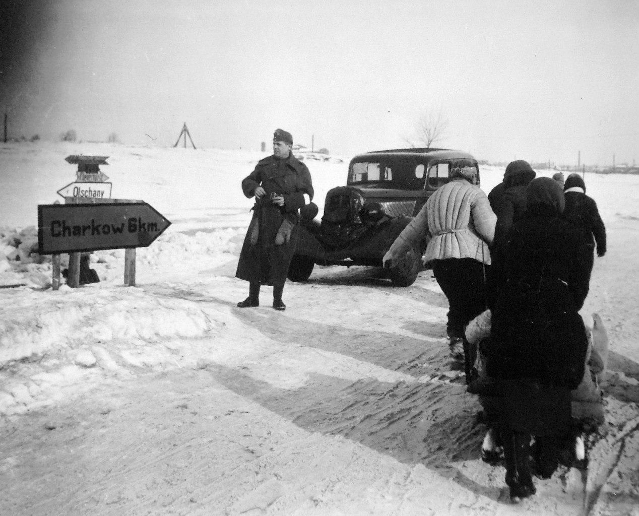 1942. Мирные жители проходят мимо венгерского солдата с автомобилем возле дорожного указателя на Харьков