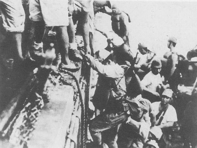Japanese troops load onto a destroyer in preparation for a