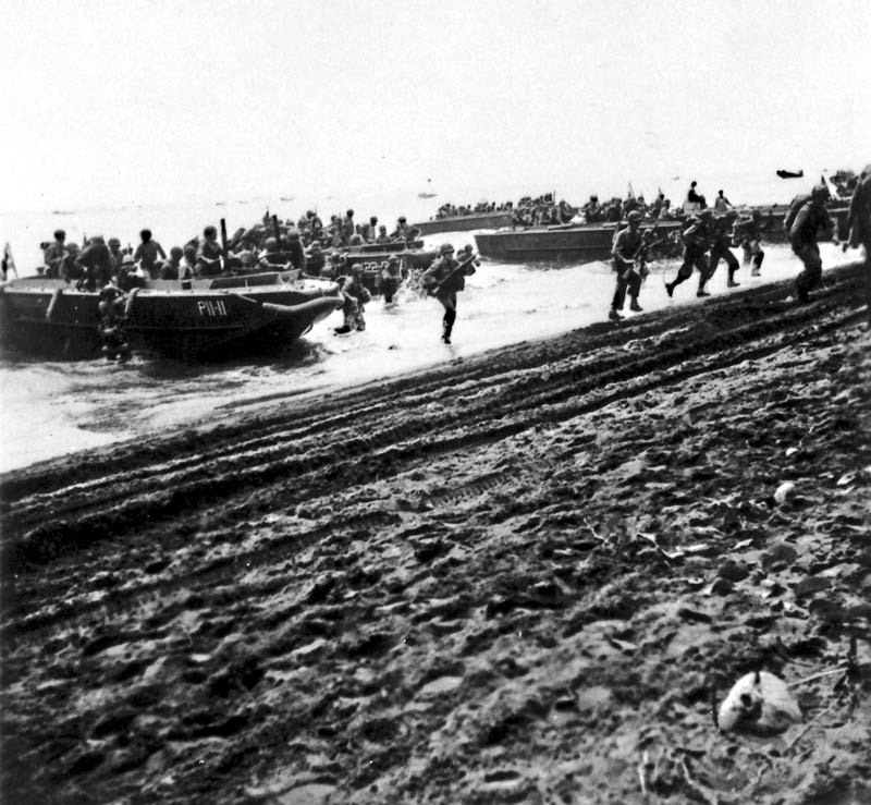 U.S. First Division Marines storm ashore across Guadalcanal's beaches on D-Day, August 7, 1942, from the attack transport USS Barnett (AP-11) and the attack cargo ship USS Fomalhaut (AK-22). The invaders were surprised at the lack of enemy opposition.
