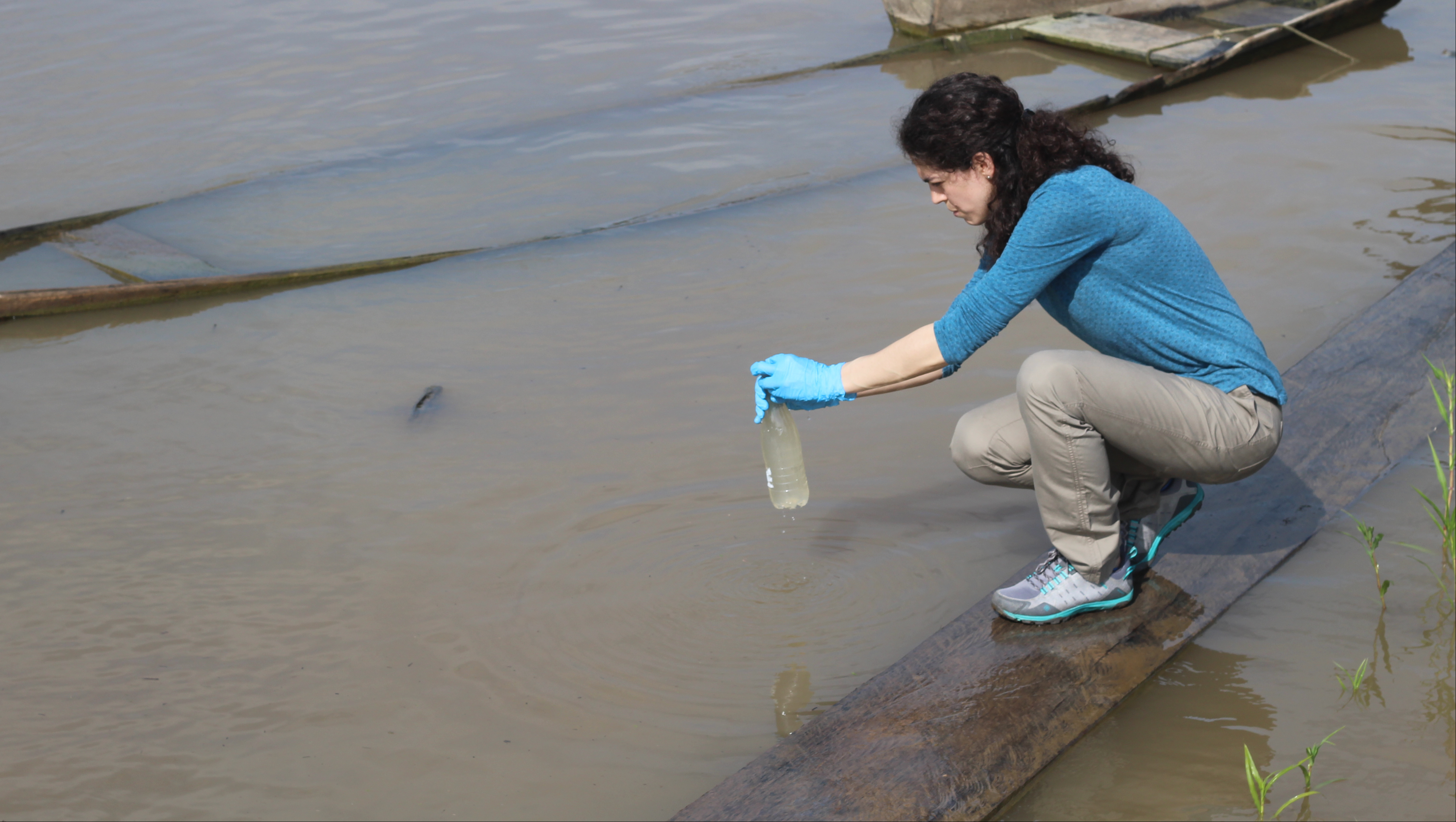 A woman taking a water sample from a river in Colombia.