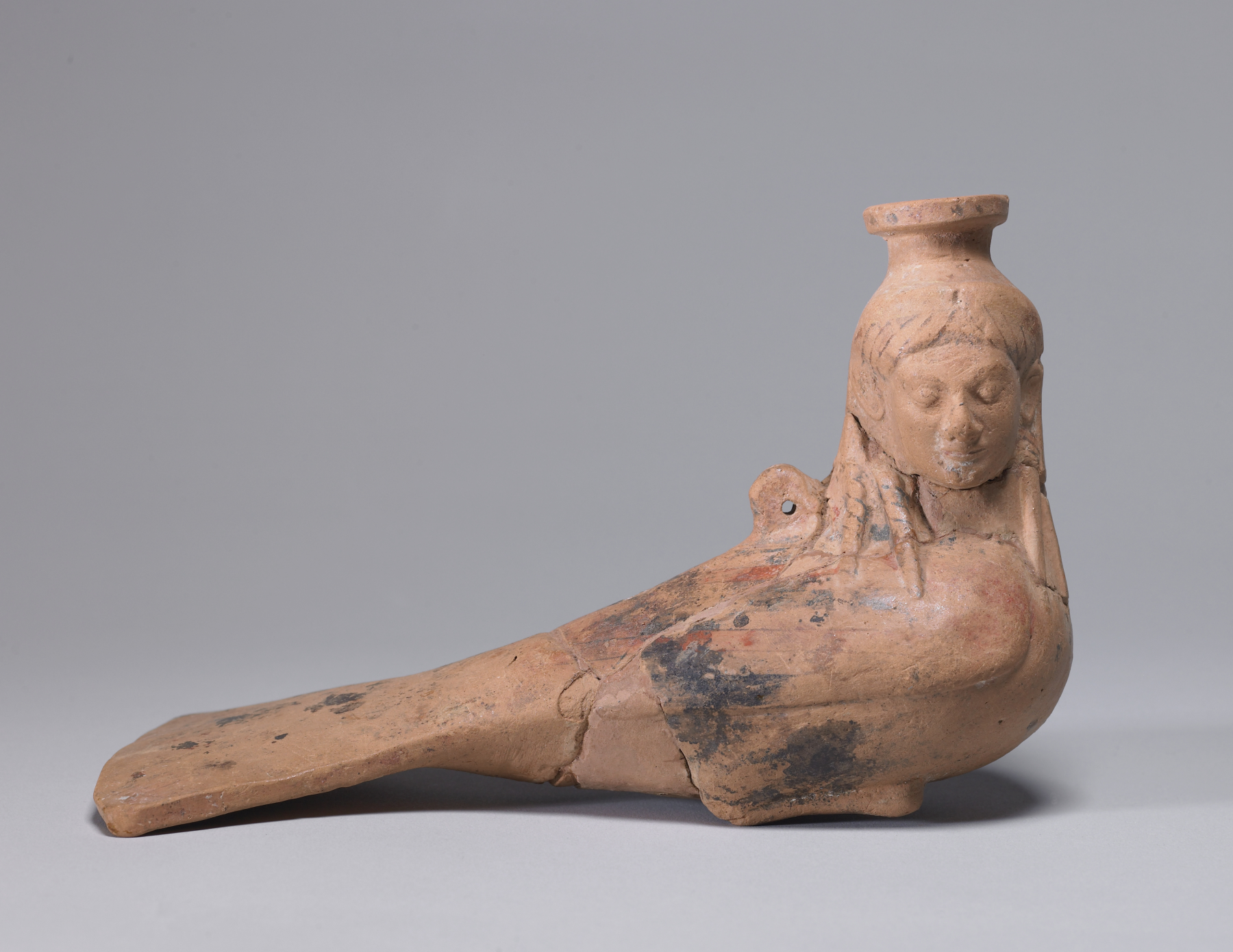 This East Greek type of terracotta perfume vase takes the form of a siren, a mythical creature with a woman's head and a bird's body, known for her connections to the underworld and for her mesmerizing power over men. A pierced lug for hanging is attached to her back. circa 540 BC (Archaic) Currently in the collection of The Walters Art Museum, Baltimore, Maryland (purchased during the sale of Joseph Brummer Collection, pt. III, Parke-Bernet Galleries, Inc., New York. June 8-9, 1949.