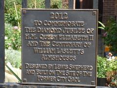 Photo of William Laslett, William Laslett's Almshouses, and Elizabeth II bronze plaque