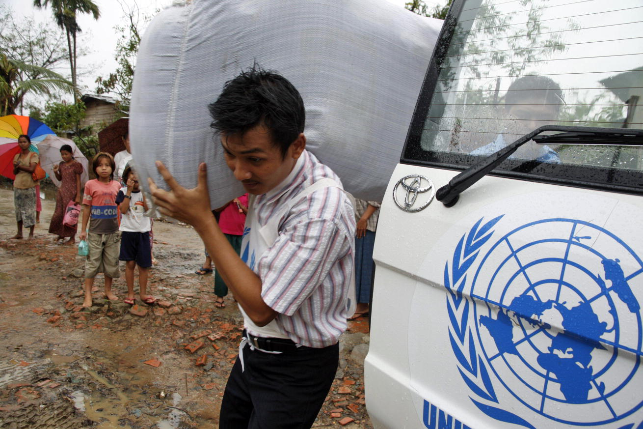 An aid worker of the United Nations High Commissioner for Refugees (UNHCR) distributes blankets to the survivors displaced by the cyclone