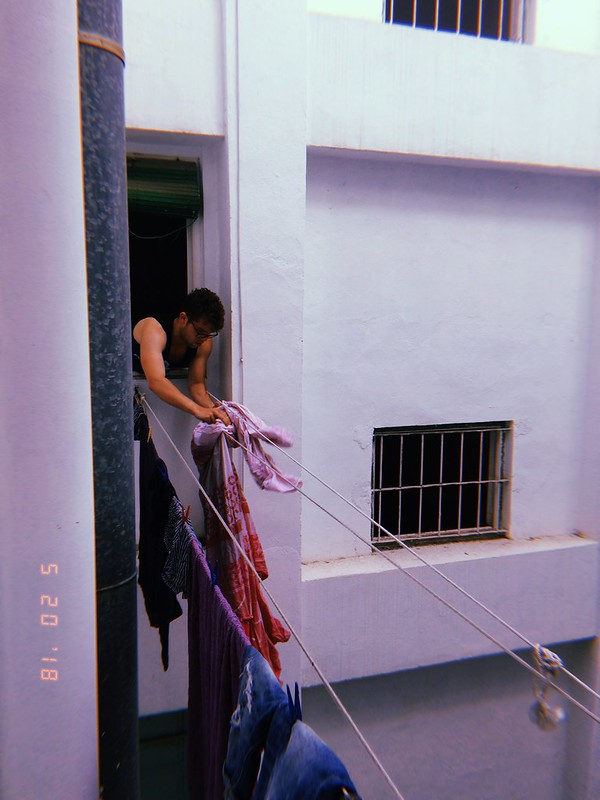 Person hanging up clothes on line from outside of window.